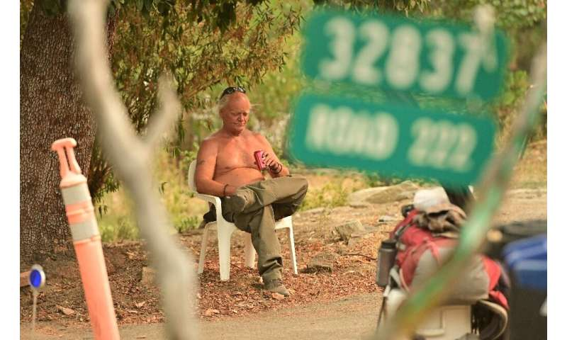 Evacuee Clay Brazil waits to be picked up during the Creek Fire in the North Fork area of unincorporated Madera County, Californ