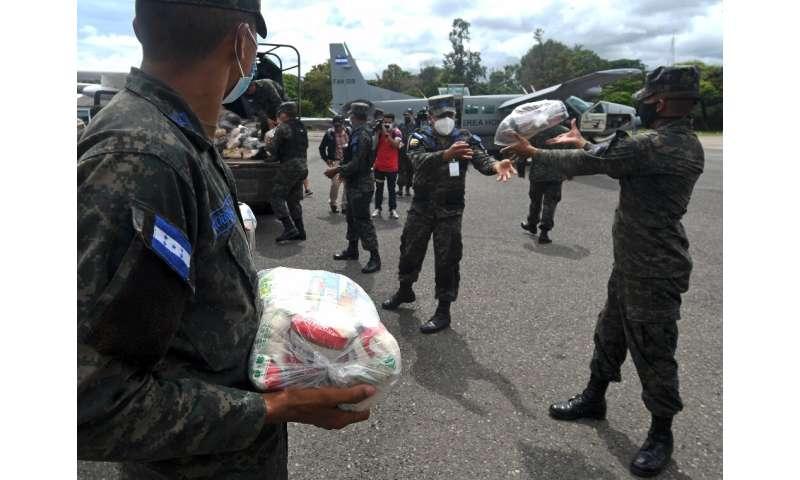 Honduran Air Force members load supplies to be taken to residents in the path of Hurricane Eta