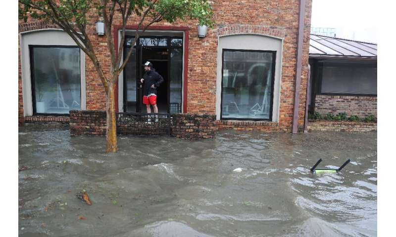 Hurst Butts looks out at a flooded street in front of his business in Pensacola, Florida, after Hurricane Sally
