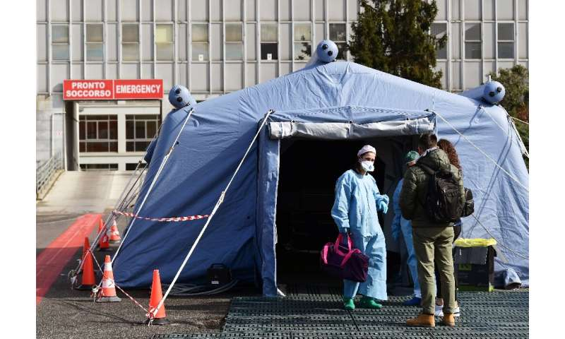 People arrive at a pre-triage medical tent in front of Cremona hospital in Italy, where the virus death toll has risen above 100