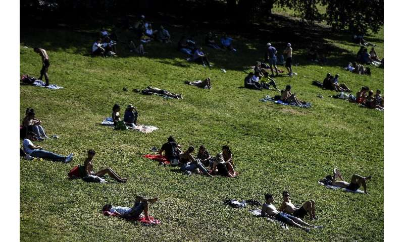 People enjoy the sun in a Paris park, but experts fear a surge in coronavirus infections