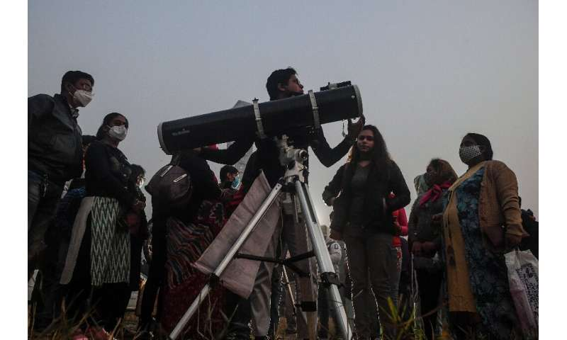 """People stand in a queue to see a """"great conjunction"""" of Jupiter and Saturn, in Kolkata, India on December 21, 2020"""