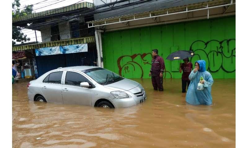 People walk past a car stuck in floodwaters in Jakarta