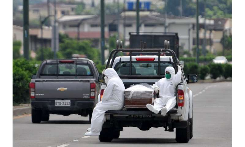 People wearing protective suits sit next to a coffin on a truck near Los Ceibos hospital in Guayaquil, Ecuador
