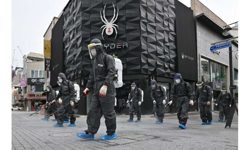 South Korean health officials from Bupyeong-gu Office wear protective gear to spray disinfectant at a shopping district in Inche