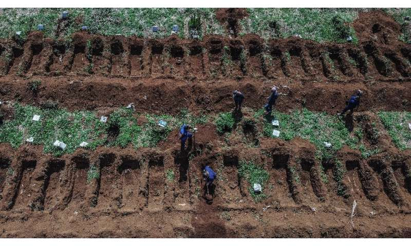 Staff dig graves at Vila Formosa cemetery, in outskirts of Sao Paulo, Brazil