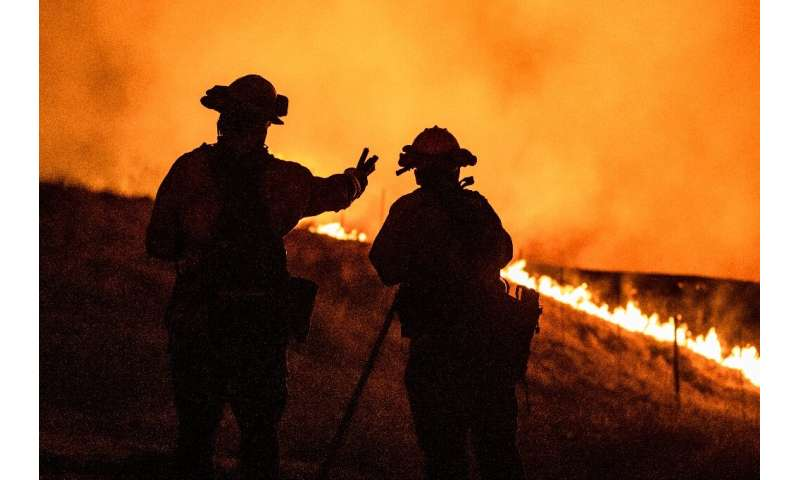 Firefighters keep watch on an approaching fire line on the outskirts of Santa Rosa, on September 27, 2020: the wildfire quickly