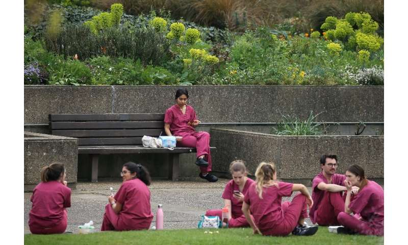 Medical staff from Britain's National Health Service (NHS) take a break outside St Thomas' Hospital in central London