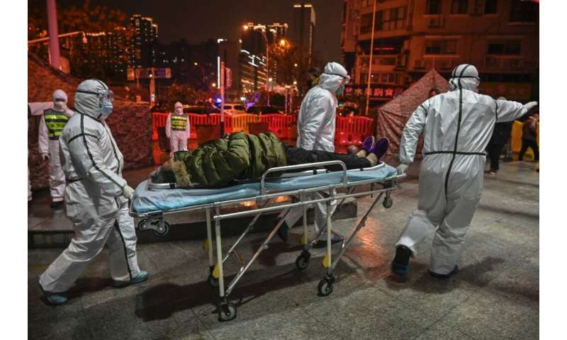 Medical staff in protective clothing arrive with a patient at a hospital in Wuhan on January 25, 2020