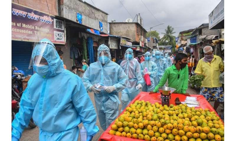Medical staff along with Hindu hardline group Rashtriya Swayamsevak Sangh volunteers wearing Personal Protective Equipment walk