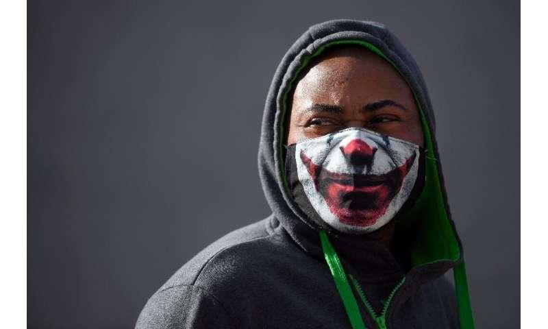 "A man wears a facemask depicting the mouth of the Batman villain ""The Joker"""