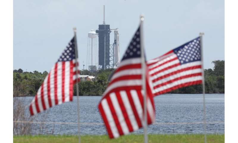 A SpaceX Falcon 9 rocket with the Crew Dragon spacecraft looms in the distance at launch complex 39A as American flags flutter i