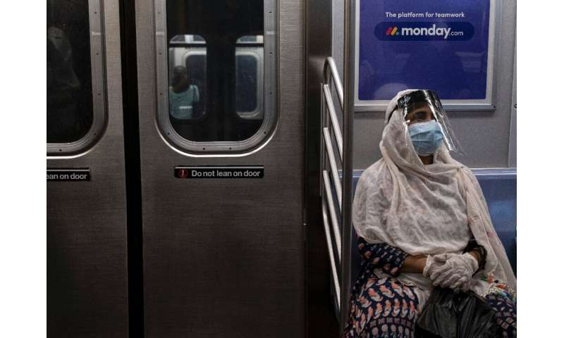 A woman wearing a face mask and shield sits in a New York subway train during rush hour amid the coronavirus pandemic on July 16
