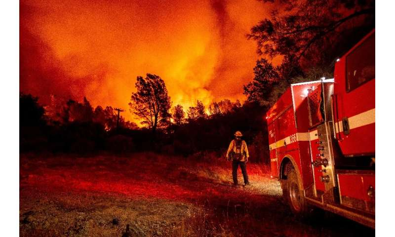 Butte County firefighters watch as flames tower over their truck at the Bear fire in Oroville, California