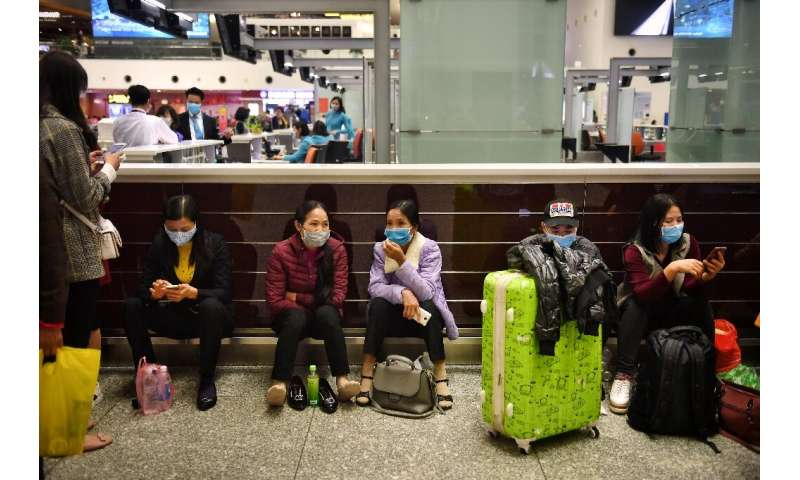 Passengers wear protective face masks in the departure hall of Noi Bai International Airport in Hanoi, Vietnam, which shares a l