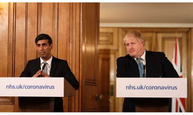 "Prime Minister Boris Johnson (R) said Britain needed to act ""like any wartime government,"" as finance minister Rishi S"