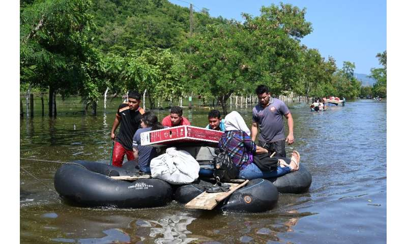 Residents evacuate a flooded area in Baracoa, Honduras on November 8, 2020