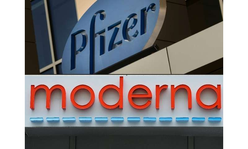 This combination of file pictures shows signs for the Pfizer and Moderna pharmaceutical companies, both in Cambridge, Massachuse
