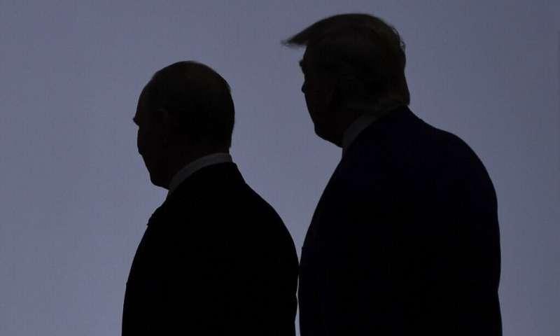 Presiden AS Donald Trump (kanan) berjalan pada 2019 dengan Presiden Vladimir Putin dari Rusia, yang disalahkan atas cyberat besar-besaran