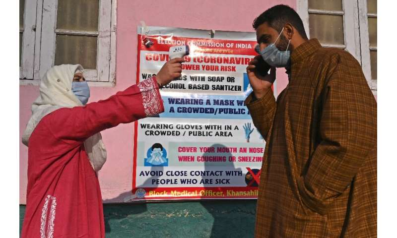 A health worker checks the temperature of a voter in India's Kashmir state