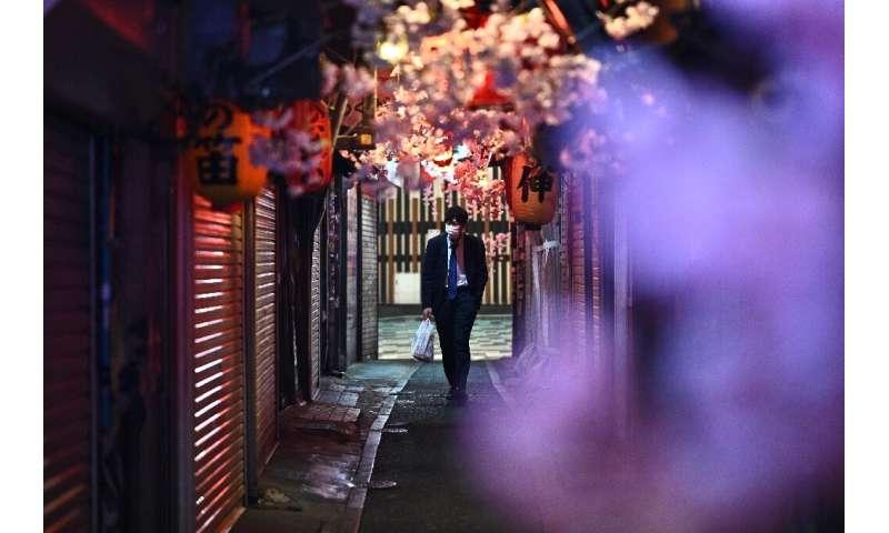 A man wearing a face mask walks along Omoide Yokocho in Tokyo