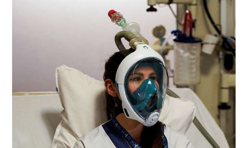 A medical worker tests a Decathlon snorkeling mask, with a 3D-printed respiratory valve fitting attached, at the Erasme Hospital