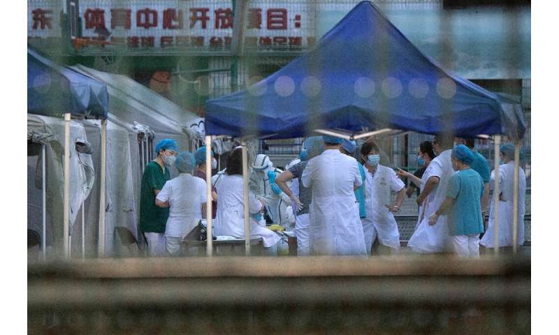 """Medical workers gather to perform COVID-19 testing in Beijing as China's capital faces an """"extremely severe"""" new outbr"""