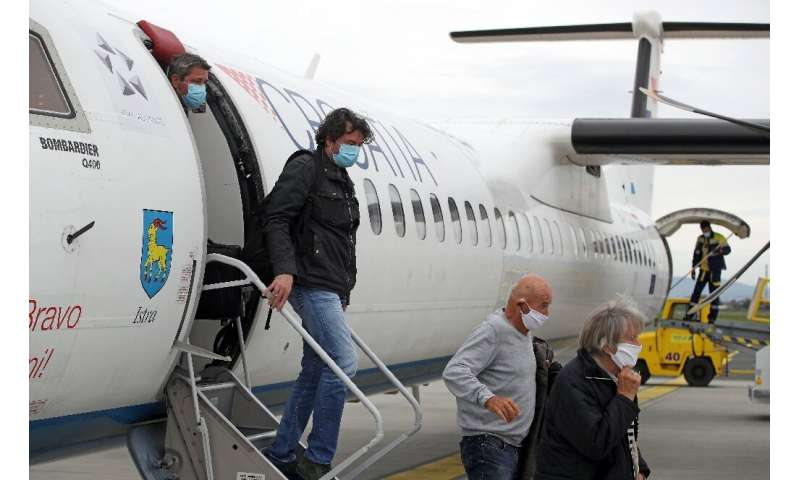 Passengers wearing masks get off a plane at Zagreb International Airport Croatia, on May 11, 2020