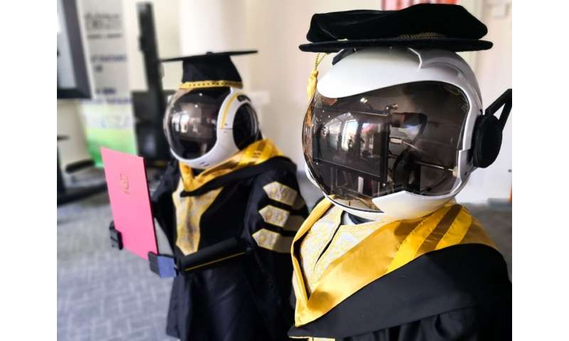 This handout photo released by the Sultan Zainal Abidin University shows two robots wearing graduation robes during a simulation