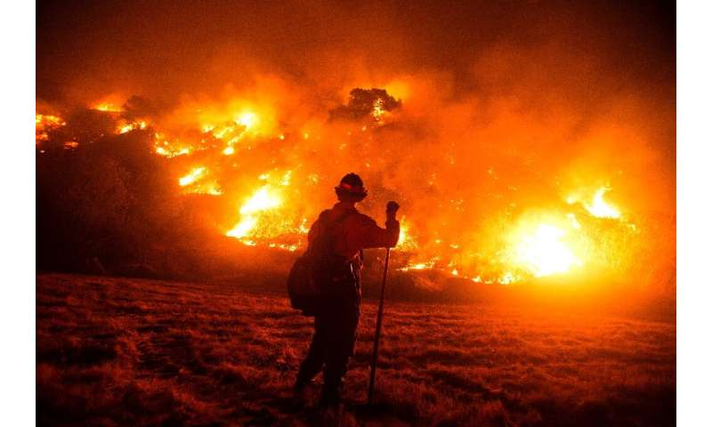 A firefighter works at the scene of the Bobcat Fire burning on hillsides near Monrovia Canyon Park in Monrovia, California on Se