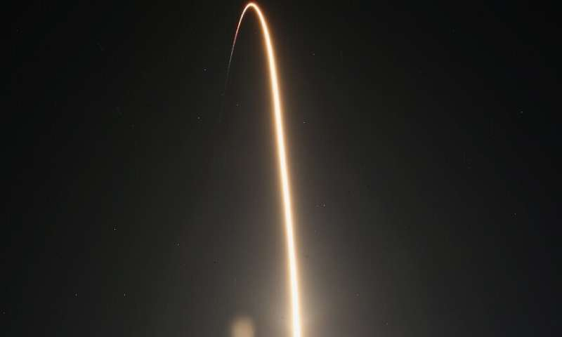 A SpaceX Falcon 9 rocket streaks toward space in this time exposure at liftoff from launch complex 39A at the Kennedy Space Cent