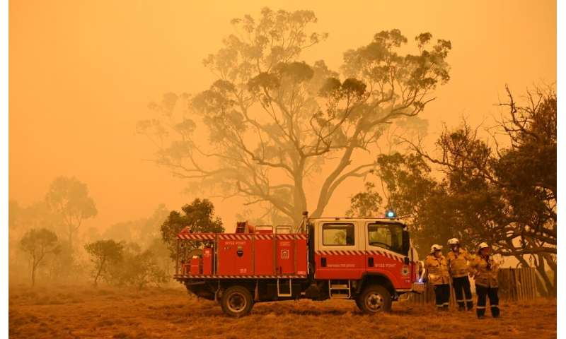 Firefighters protect a property from bushfires burning near the town of Bumbalong south of Canberra on February 1, 2020