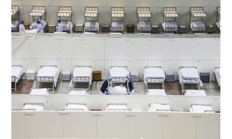 Medical staff set up beds for patients displaying mild symptoms of the coronavirus at an exhibition centre converted into a hosp