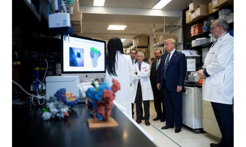 President Donald Trump tours the National Institute of Health's Vaccine Research Center in Bethesda, Maryland, as the death toll