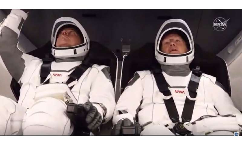 NASA astronauts Bob Behnken (L) and Doug Hurley (R) are strapped in the SpaceX Crew Dragon capsule
