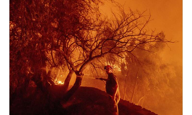Californians flee as strong winds push fire through canyons