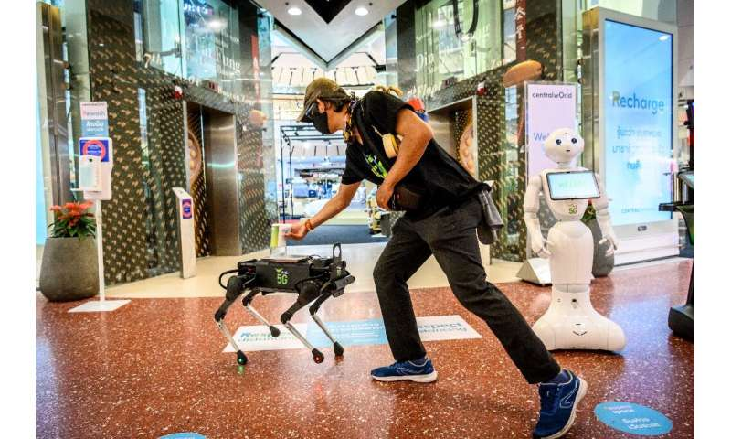 A 5G K9 robot distributes hand sanitiser to a visitor at a shopping mall in Bangkok