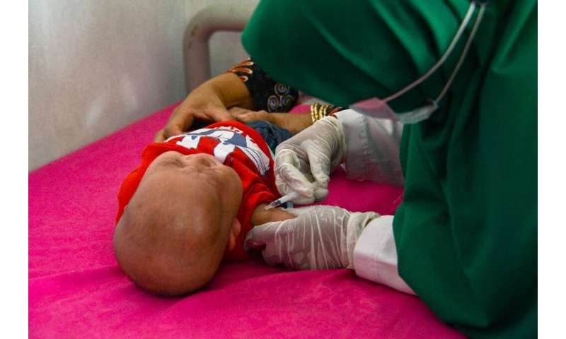 A baby receives the Bacillus Calmette–Guerin (BCG) vaccine for tuberculosis at an integrated services post in Banda Aceh, Indone