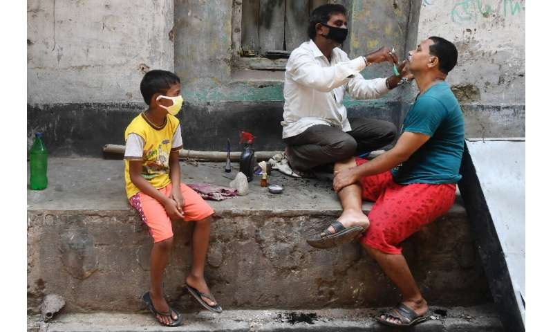 A barber wearing a facemask attends to a customer in Kolkata during a government-imposed nationwide lockdown