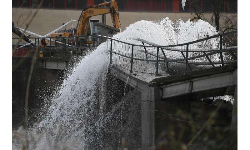 A broken pipe on a damaged bridge flows into the flooded Ter near Girona