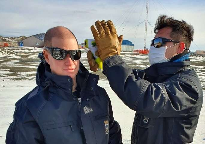 A Chilean Air Force doctor checking the temperature of personnel at the Eduardo Frei Antarctic base on the Fildes Peninsula, on