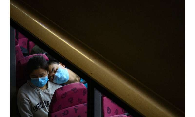 A couple wearing face masks sit in the upper deck of a double-decker bus in Hong Kong