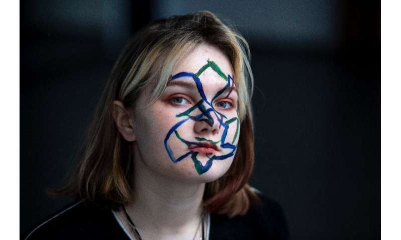 Activists in Moscow protesting the use of facial recognition technology paint geometrical shapes and lines on their faces as thi