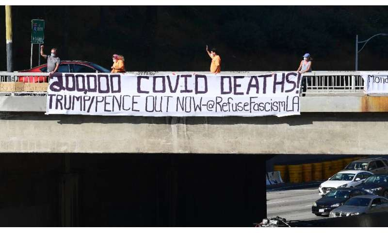 """Activists unfurl a banner reading """"200,000 Covid Deaths! Trump/Pence Out Now"""" over a freeway in  Los Angeles"""