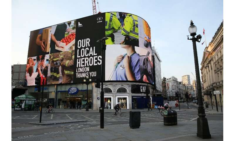 """A display of images in Piccadilly Circus in central London accompanies a message of support for """"our local heroes"""" wor"""