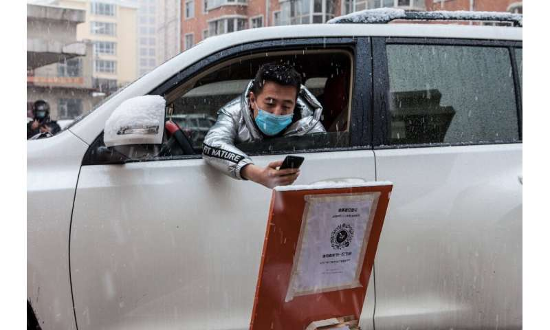 A driver scans a QR code to register information before entering a community in the border city of Suifenhe, in China's northeas
