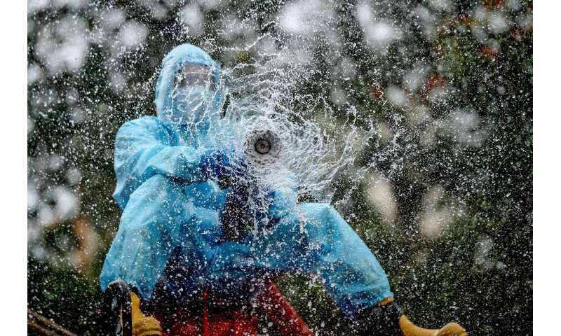 A firefighter sprays disinfectant as a preventive measure against the spread of the COVID-19 coronavirus in a containment zone i