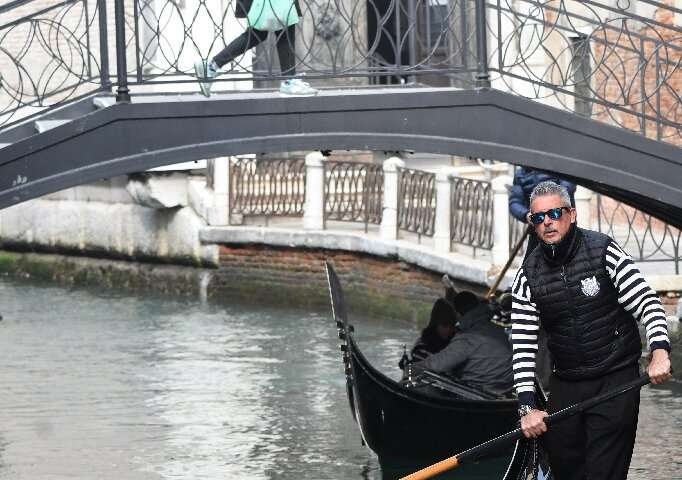 A gondolier steers tourists in facemasks along a canal in Venice
