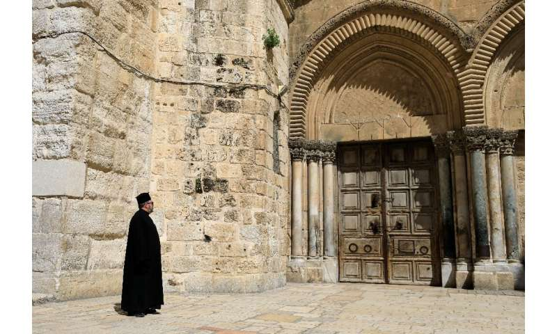 A Greek Orthodox priest gazes at the closed door of the Church of the Holy Sepulchre in the Old City of Jerusalem following the