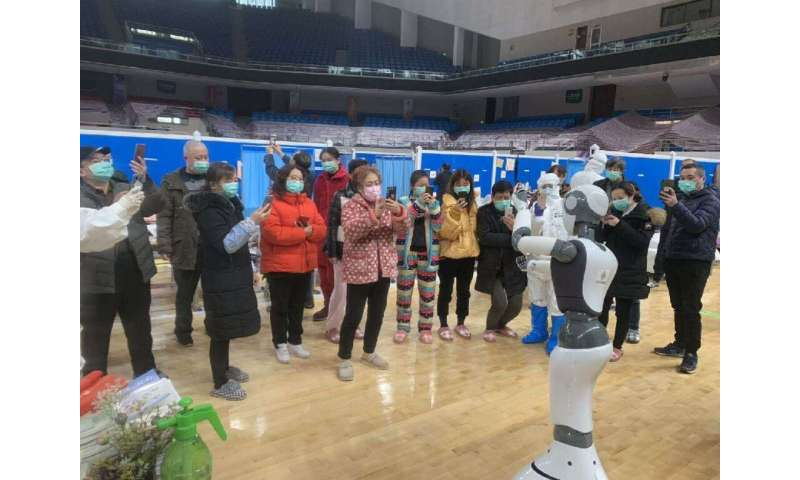 A handhout picture provided by CloudMinds shows Wuhan smart field hospital staff looking at an XR1 robot being deployed for coro